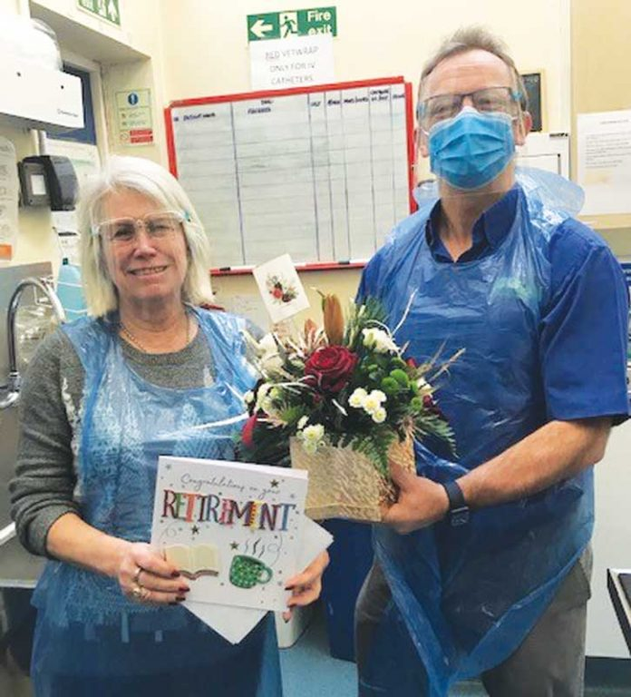 Linda Rogers is presented with a bouquet of flowers by Marcus Johnstone.