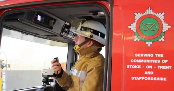 A firefighter sitting in the a fire engine.