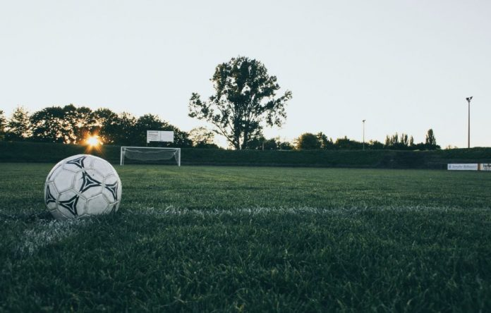 A close up shot of a football in front of a goal.