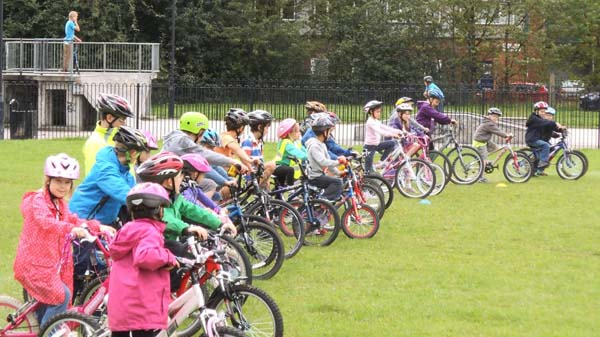 Children lined up on their bikes in a field.