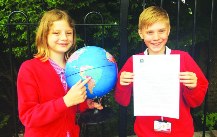 From left, head boy Wilson Gardner, (11), and head girl Amelia Banks, (11), receiving the letter on behalf of year six pupils.